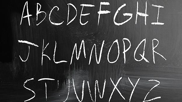 Mit Kreide geschriebene Buchstaben von A bis Z auf einer Wandtafel.