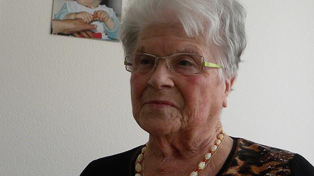 Die Seniorin mit grau-weissen Haaren trägt eine Brille, eine Glasperlenkette und einen braun-schwarzen Pullover.