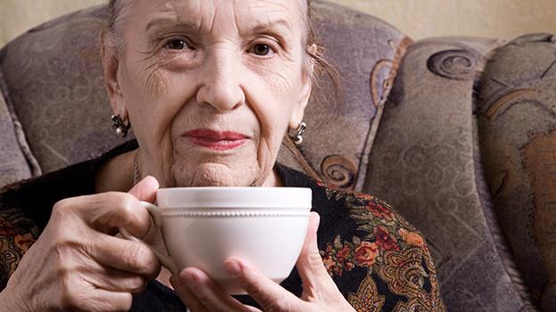 Eine ältere Frau sitzt in einem Sessel und trinkt eine Tasse Kaffee.