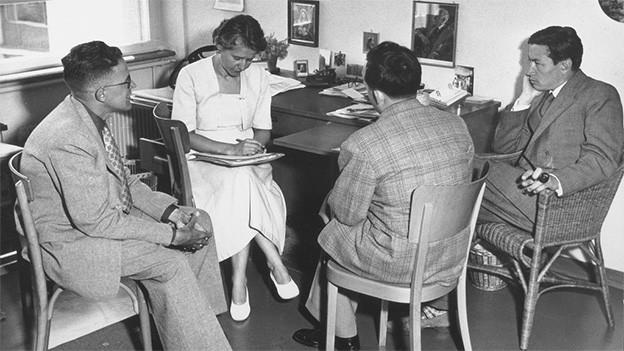 Schwarz-Weiss Fotografie mit drei Männern und einer Frau.
