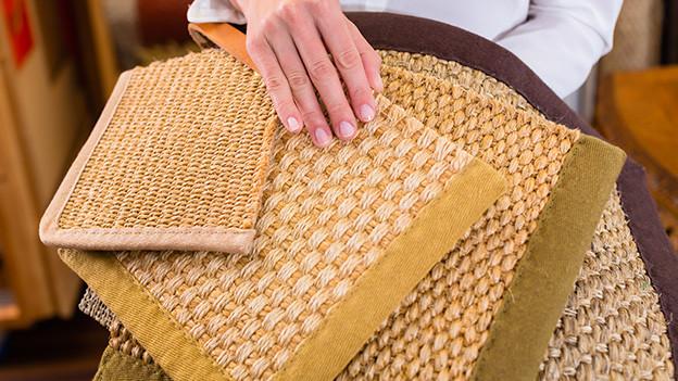 Eine Verkäuferin zeigt verschiedene Teppichmuster.