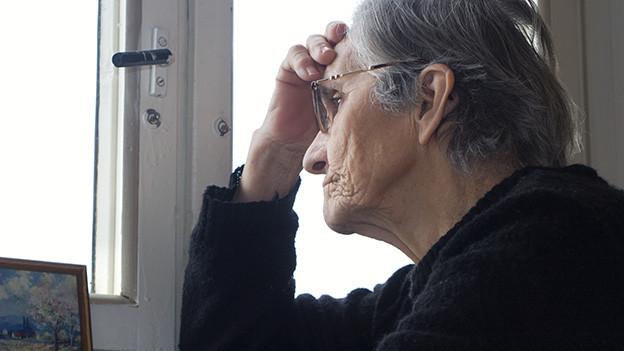 Eine alte Frau sitzt nachdenklich und etwas traurig am Fenster.