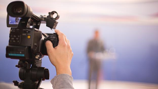 Eine verschwommene Silhouette eines Moderators, davor eine Fernsehkamera.