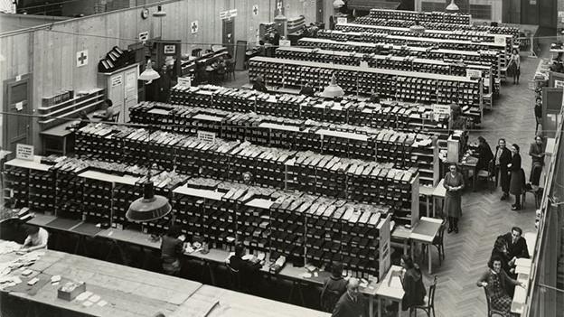 Schwarz-Weiss Fotografie von einem grossen Saal, in mehreren Reihen viele kleine Boxen stehen.