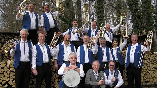 Die Musikanten tragen weisse Hemden sowie blaue Westen und posieren mit ihren Instrumenten in einem Wald fürs Gruppenfoto.