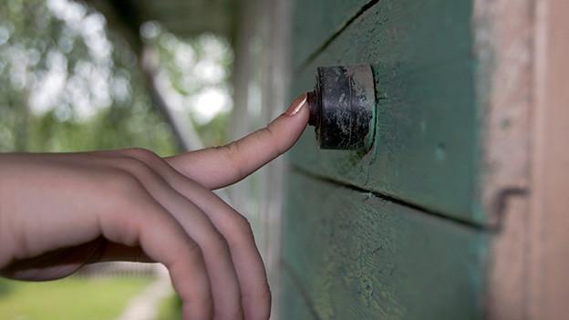Eine Frauenhand an einer Türklingel.