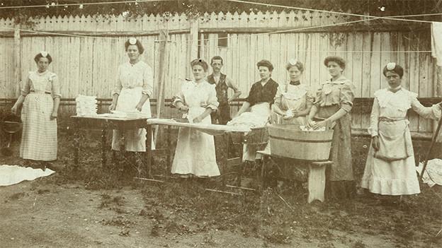 Alte Fotografie mit Hausangestellten, die in einem Garten vor grossen Bottichen stehen.
