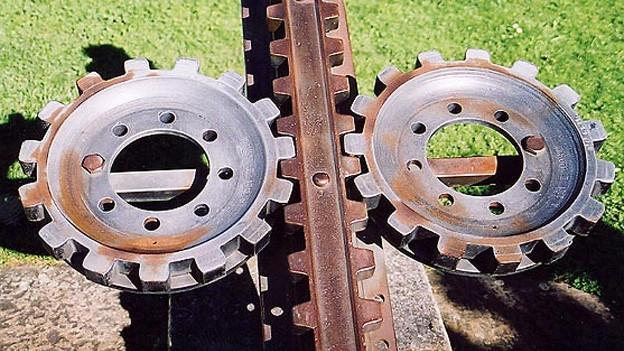 Zwei waagrecht liegende Zahnräder links und rechts einer Zahnstange.