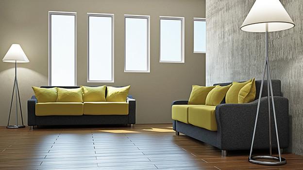 Wohnzimmer mit zwei grau-grünen Sofas und zwei Stehlampen.