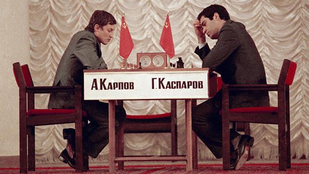 Die beiden Schachspieler sitzen sich an einem Schachtisch hochkonzentriert gegenüber.