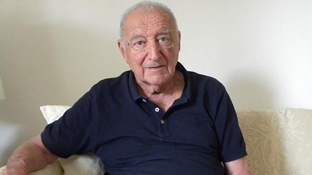 Der 85-Jährige sitzt auf einem weissen Sofa in seinem Wohnzimmer.
