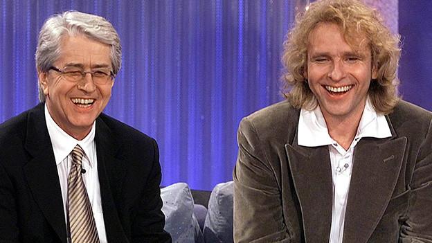 Die zwei Moderatoren sitzen auf einem grauen Sofa, hinter dem ein blauer Vorhang hängt.