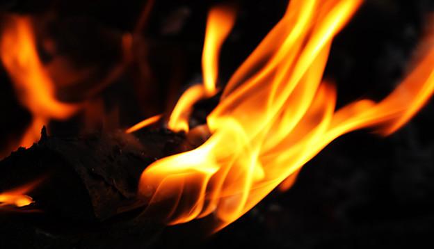 Flamme einer brennenden Fackel in einer dunklen Nacht.