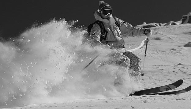 Ein Skifahrer im aufspritzenden Pulverschnee.