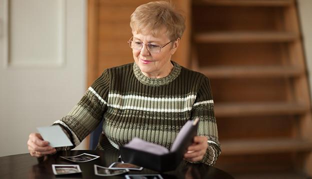 Eine ältere Frau sitzt an einem Tisch und blättert in ihrem Fotoalbum.