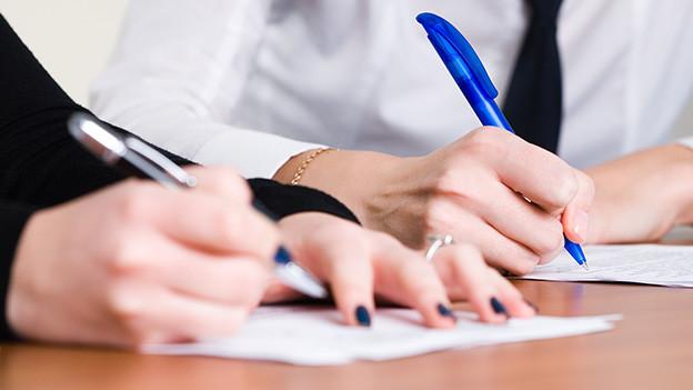Hände einer Frau und eines Mannes, die ihre Unterschrift auf ein Blatt Papier setzen.