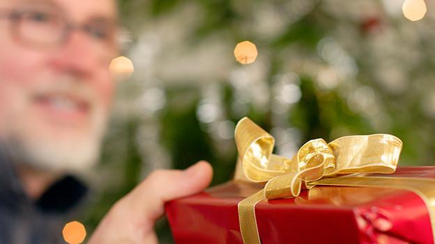 Ein älterer Mann mit Brille übergibt jemandem ein Geschenk in rotem Geschenkpapier mit goldener Schleife.