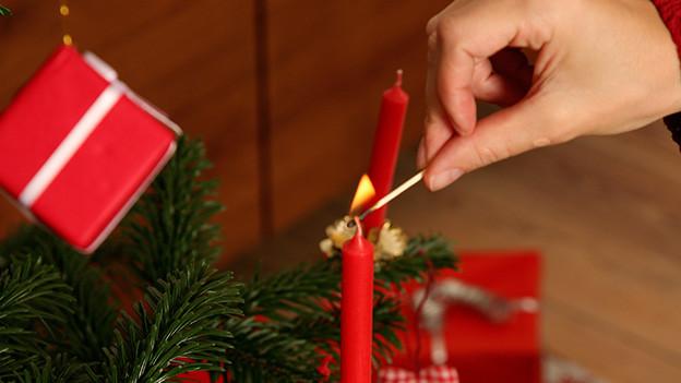Mit einem Streichholz wird eine rote Kerze am Weihnachtsbaum angezündet.