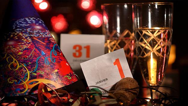 Kalenderblätter, Champagnergläser und Party-Dekoration.