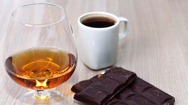Ein Schnapsglas, eine Tasse Kaffee und ein Stück Blockschokolade auf einem Tisch.