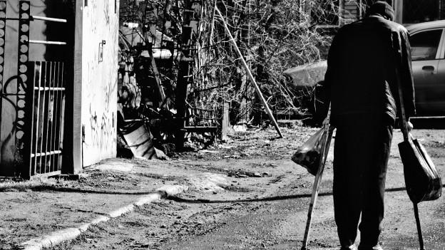 Mann mit Krücken auf Strasse.