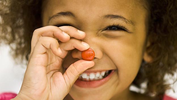 Ein Kind hält eine kleine Kugel Schokolade vor dem Gesicht.