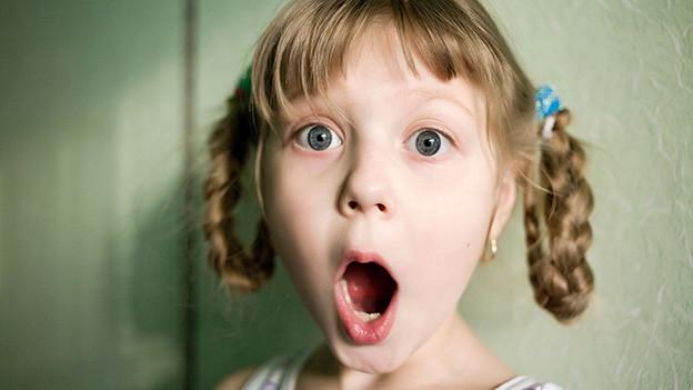 Ein kleines Mädchen mit hochgesteckten Zöpfen blickt empört und mit offenem Mund in die Kamera.