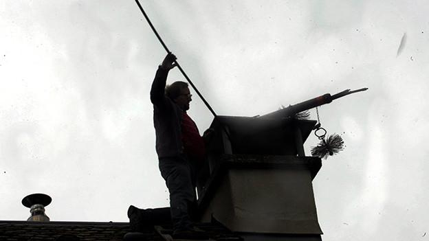 Ein Schornsteigfeger steht auf einem Dach und reinigt den Kamin.