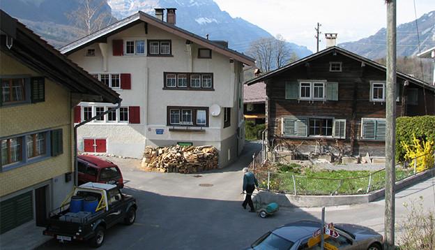 Dorfansicht mit Häusern, Strasse und einem Mann, der eine Schubkarre zieht.