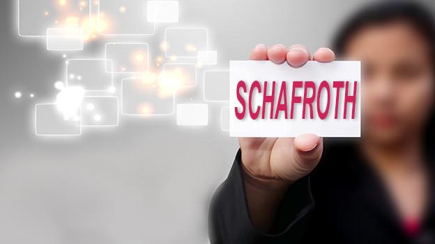 Konturen einer Frau, die eine Visitenkarte mit dem Namen Schafroth zeigt.