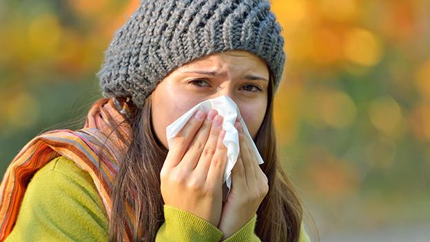 Eine junge Frau mit Mütze putzt sich die Nase und macht einen kränkelnden Eindruck.