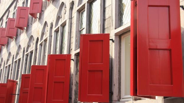 mehrere Fensterladen in rot stehen offen.