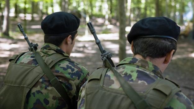Zwei Schweizer Soldaten mit Gewehren bewaffnet in einem Wald.