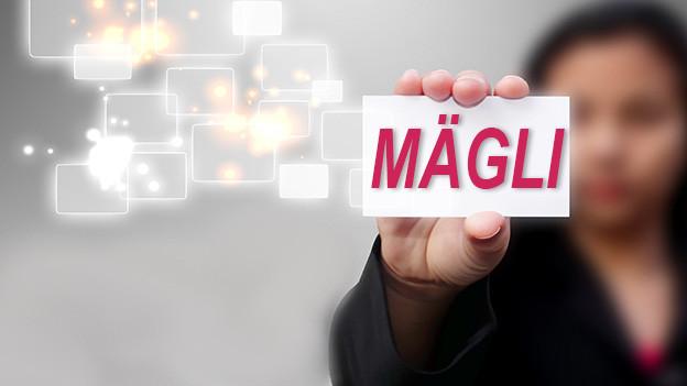 Konturen einer Frau, die eine Visitenkarte mit dem Namen Mägli zeigt.