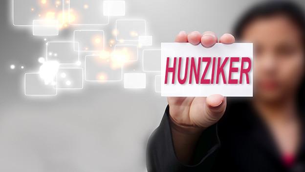 Konturen einer Frau, die eine Visitenkarte mit dem Namen Hunziker zeigt.