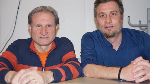 Zwei Männer an Tisch.