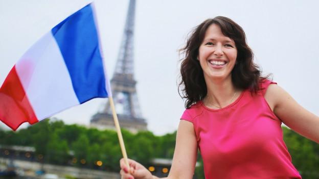 Frau mit Frankreich-Fahne vor Eiffelturm.