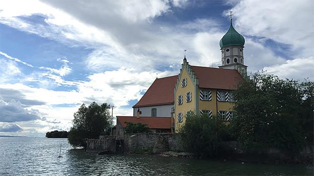 Ein stattliches Haus mit Turm am Seeufer.