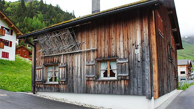 Ein altes Holzhaus an einer Strassenecke.
