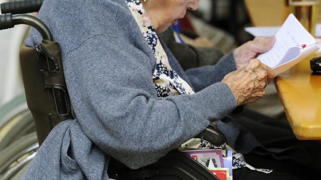 Seniorin liest einen Brief am Tisch in der Kantine.