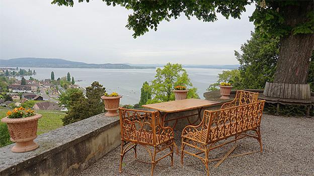 Gartenmöbel auf einer Terrasse mit Blick auf den See.