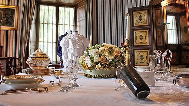 Kleider und Geschirr als Ausstellungsstücke in einem Esszimmer.