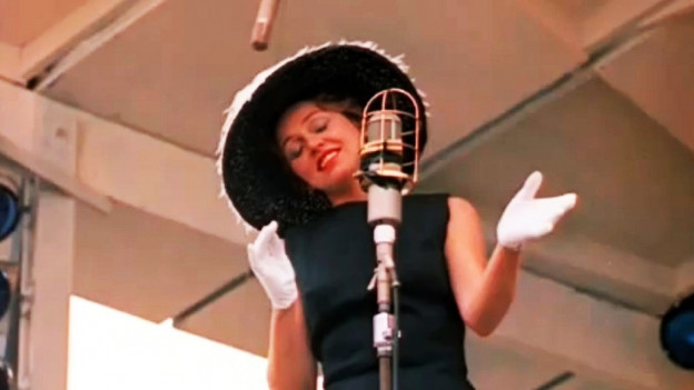 Anita O'Day mit extravagantem Hut während eines Auftritts.