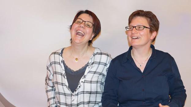 Die beiden Frauen lachen ausgelassen in die Kamera.