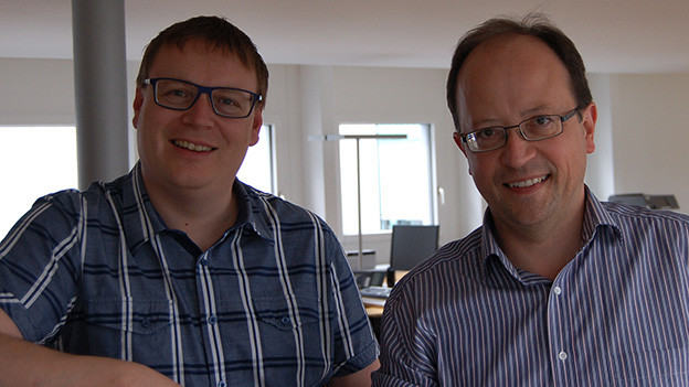 Moderator und Gast stehen nebeneinander vor einem Büromöbel.