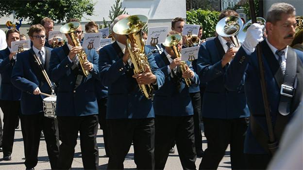 Uniformierte Blasmusikanten während eines Umzugs.