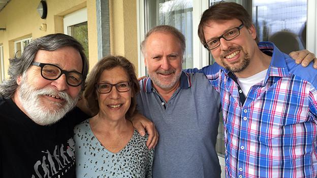 Gruppenbild mit drei Männern und einer Frau, die auf einer Terrasse stehen.
