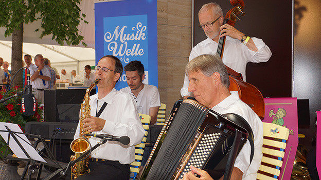 Eine Volksmusikformation an einem sonnigen Tag auf einer Konzertbühne.
