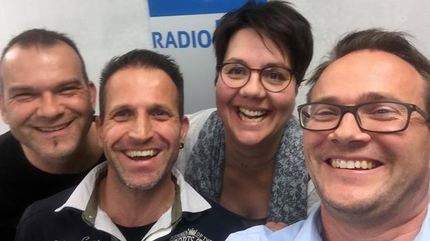 Ein lustiges Selfi bei dem drei Männer und eine Frau in die Kamera lachen.