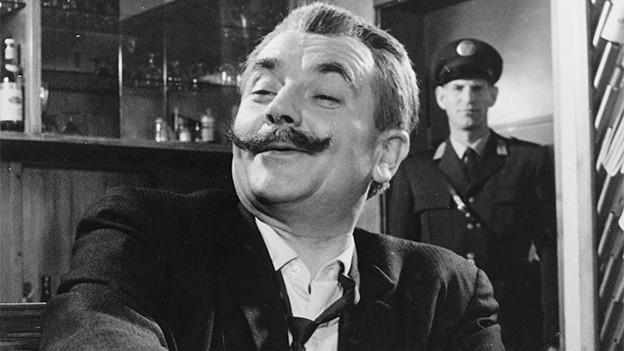 Schwarz-Weiss-Fotografie von einem dunkelhaarigen Mann mit dickem Schnurrbart.